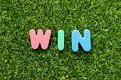 Toy foam letter in word win on green grass background