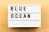 Light box with word blue ocean on wood background