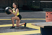 Exercise. Sport woman doing leg workout with med ball outdoors