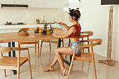 Woman having breakfast in kitchen in morning