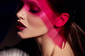 Makeup beauty. Woman model with dark lipstick under pink light