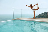 Yoga. Woman in swimsuit stretching legs near swimming pool