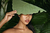 Beauty. Asian woman model with green leaf over face portrait