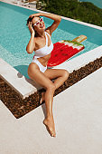 Summer fashion. Woman in swimsuit, sunglasses near swimming pool