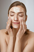 Face skin care. Woman cleaning facial skin with foam soap