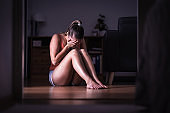 Victim of sexual harassment, domestic violence or abuse. Young sad woman crying and sitting on the floor at home. Ashamed, scared or lonely lady suffering emotional pain.