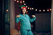 Funny Pregnant Woman Celebrating Christmas in Pajamas