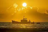 Fishing boats out to sea at dawn