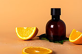 Cosmetic bottle container with fresh orange slices on an orange background,