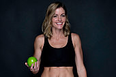 One person / waist up / front view of 20-29 years old adult beautiful caucasian young women / female standing / exercising in front of black background wearing sports clothing / sports bra / shorts / running shorts who is smiling / happy / cheerful