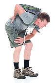 Friendly male hiker has a backache