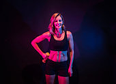 One person / waist up / front view of 20-29 years old adult beautiful caucasian young women / female standing / exercising in front of black background / multi-colored background / colored background who is smiling / happy / cheerful