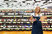 One person / waist up of blond hair female / young women owner / retail occupation standing at the cellar / liquor store / supermarket in the store / shopping mall wearing apron who is smiling / happy / cheerful who is buying / shopping / working
