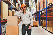 One man only / one person / waist up / front view of male / young men manual worker / photography standing at the warehouse / distribution warehouse / factory / storage compartment / storage room in front of merchandise who is talking