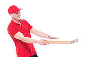 One man only / waist up of 20-29 years old adult handsome people caucasian male / young men pizza delivery person / delivery person in front of white background wearing jeans / polo shirt / baseball cap / trucker's hat who is delivering / food