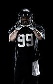 Waist up / one man only / one person / front view of adult handsome people caucasian young men / male american football player / athlete standing in front of black background wearing helmet / sports helmet and celebration and using sports ball