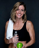 Waist up / one person of 20-29 years old adult beautiful caucasian female / young women standing in front of black background wearing sports clothing / sports bra / shorts / running shorts who is smiling / happy / cheerful and holding water bottle