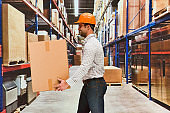 One man only / one person / waist up / front view of handsome people male / young men manual worker / photography standing at the warehouse / distribution warehouse / factory / storage compartment / storage room in front of merchandise