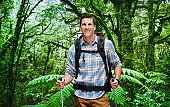 One man only / one person / waist up / front view of male / young men backpacker / tourist / tourist hiking / standing in front of nature in the woodland who is outdoors wearing lumberjack shirt / plaid shirt / khaki pants / backpack / sky