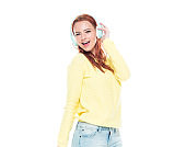 One person / waist up of 18-19 years old beautiful redhead caucasian young women teenage girls in front of white background wearing jeans who is smiling / happy / cheerful / listening who is sweating and using headphones / music