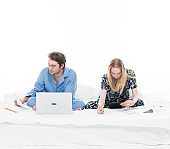 Two people sitting up in bed working
