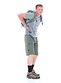Front view / one person / full length of 20-29 years old caucasian young men / male backpacker hiking / standing / physical injury in front of white background wearing shorts / backpack / hiking boot / t-shirt who is in pain / illness and holding bag