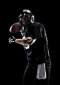 Waist up / one man only / one person / front view of adult handsome people caucasian young men / male american football player / athlete standing in front of black background wearing helmet / sports helmet who is a sex symbol / of muscular build