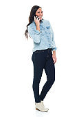 Full length / side view / profile view / one person of adult beautiful brown hair / long hair caucasian female / young women / mid adult women / mid adult standing wearing button down shirt / shirt / jeans / pants and holding mobile phone
