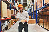 One man only / one person / waist up / front view of male / young men manual worker / photography standing at the warehouse / distribution warehouse / factory / storage compartment / storage room in front of merchandise who is delivering