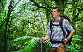 One man only / one person / waist up / side view / profile view of male / young men backpacker / tourist / tourist hiking / standing in front of nature in the woodland who is outdoors wearing lumberjack shirt / plaid shirt / khaki pants / backpack