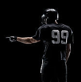 Waist up / one man only / one person / rear view / back of adult handsome people caucasian young men / male american football player / athlete / presenter standing in front of black background wearing helmet / sports helmet who is showing / pointing