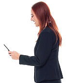 Side view / profile view / one person / waist up / portrait of 20-29 years old adult beautiful redhead / long hair caucasian female / young women businesswoman / business person standing wearing businesswear / a suit and holding mobile phone