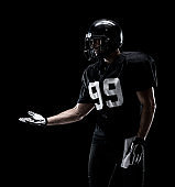 Waist up / one man only / one person / sideways glance / looking away of adult handsome people caucasian young men / male american football player / athlete / presenter standing in front of black background wearing helmet / sports helmet / presenting
