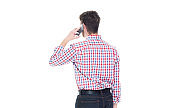 One person / rear view / waist up of 20-29 years old adult handsome people caucasian young men / male standing in front of white background wearing gingham / jeans who is talking and holding mobile phone / using smart phone