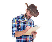 One man only / one person / waist up / front view / looking down of 30-39 years old adult handsome people caucasian male / young men cowboy standing in front of white background who is smiling / happy / cheerful / cool attitude who is writing