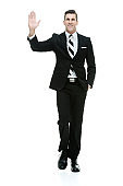 One man only / full length / front view / looking at camera of 30-39 years old adult handsome people caucasian male / young men business person / businessman walking in front of white background wearing businesswear / a suit and waving / greeting