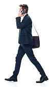 Full length / side view / profile view / one man only / one person of 20-29 years old adult handsome people brown hair / with beard caucasian male / young men manager / businessman / business person walking wearing a suit and holding bag