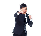 One man only / one person / front view / waist up of 20-29 years old adult handsome people chinese ethnicity / east asian ethnicity male / young men standing who is serious and showing fist who is in fighting stance / fighting / punching