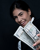 Headshot / portrait of 20-29 years old beautiful / long hair latin american and hispanic ethnicity young women / female in front of black background who is smiling / happy / cheerful and holding currency / european currency / us currency