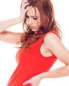 Waist up of 18-19 years old beautiful redhead caucasian young women teenage girls / physical injury in front of white background wearing dress and high heels who is in pain / illness with backache / bad posture