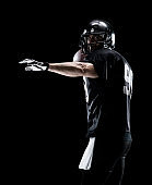 Waist up / one man only / one person / side view / profile view of adult handsome people caucasian young men / male american football player / athlete standing in front of black background wearing helmet / sports helmet who is throwing / catching