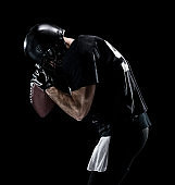 Waist up / one man only / one person / side view / profile view of adult handsome people caucasian young men / male american football player / athlete standing in front of black background wearing helmet / sports helmet who is lost