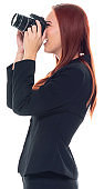 Side view / profile view / one person / waist up / portrait of 20-29 years old adult beautiful redhead / long hair caucasian female / young women photographer / photography / businesswoman / business person standing wearing businesswear / a suit