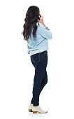 Full length / rear view / back / one person of adult beautiful brown hair / long hair caucasian female / young women / mid adult women / mid adult standing wearing button down shirt / shirt / jeans / pants who is talking and holding mobile phone