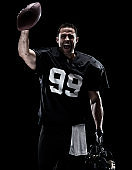 Waist up / one man only / one person / front view of adult handsome people caucasian young men / male american football player / athlete standing in front of black background wearing helmet / sports helmet and winning and using sports ball