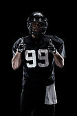 Waist up / one man only / one person / front view of adult handsome people caucasian young men / male american football player / athlete standing in front of black background wearing helmet / sports helmet and celebration / cheering / showing fist