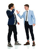 Full length / two people / one teenage boy only of 18-19 years old handsome people caucasian male / young men / brother friendship / boys / teenage boys / hipster - person / businessman / business person standing wearing a suit / cool attitude