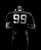 Waist up / one man only / one person / rear view / back of handsome people caucasian young men / male american football player / athlete standing in front of black background wearing helmet / sports helmet who is lost and using sports ball