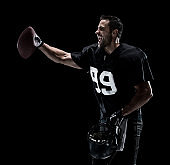 Waist up / one man only / one person / side view / profile view of adult handsome people caucasian young men / male american football player / athlete standing in front of black background wearing helmet / sports helmet and winning