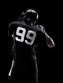 Waist up / one man only / one person / rear view / back of adult handsome people caucasian young men / male american football player / athlete standing in front of black background wearing helmet / sports helmet who is throwing / catching